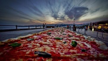 epa05315969 A general view of a Neapolitan pizza made to break the world record for the longest pizza ever made, by making a two kilometers margherita (16 inch wide) pizza stretching along the city waterfront, in Naples, Italy, 18 May 2016.  EPA/CIRO FUSCO